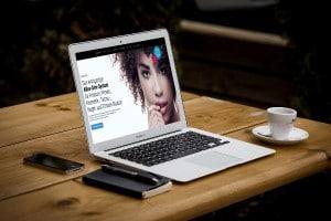 Das Bild zeigt einen Laptop, der auf dem Tisch steht und die Startseite von der zertifizierten Kassensoftware studiolution anzeigt